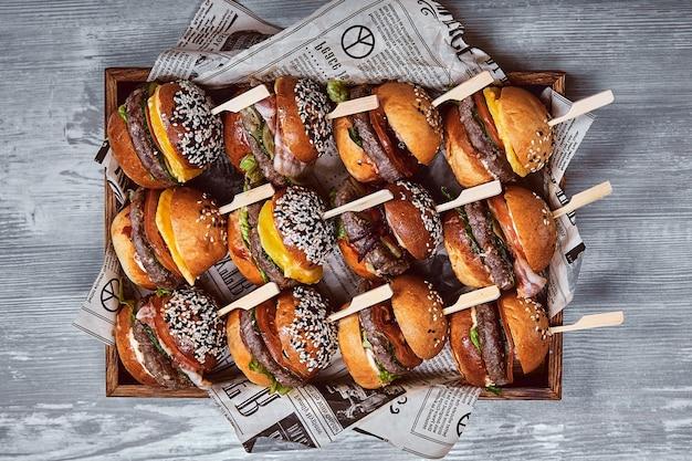 明るい背景の木製の箱においしいチーズバーガーのセットです。さまざまなハンバーガーが入った箱、会社向けのセットオファー、