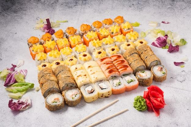 Набор вкусных суши-роллов на сером фоне