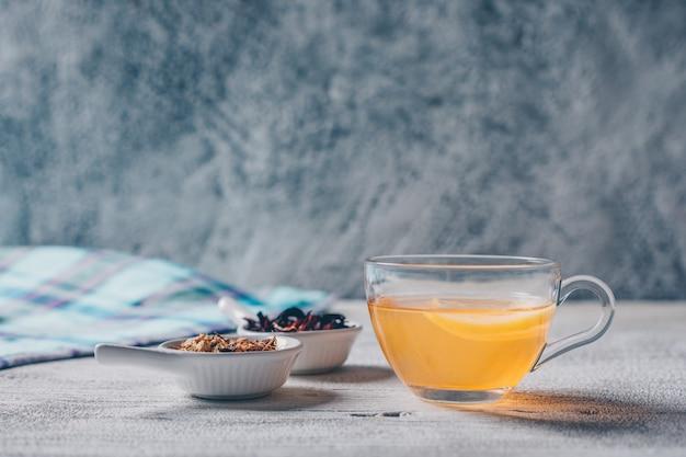 Набор чая травы и апельсинового цвета воды на сером фоне. вид сбоку.