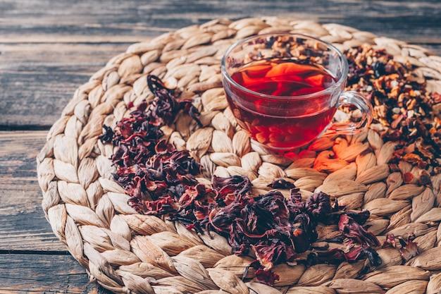 お茶のハーブと暗い背景の木の五徳でお茶のセット。ハイアングル。
