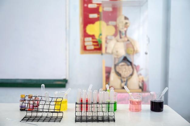 科学クラスの実験室の机の上の試験管とカラフルなビーカーと実験物質のセット