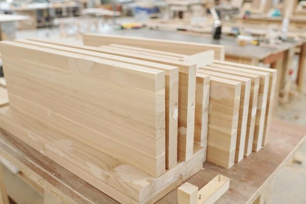 現代の工場のワークショップ内のエンジニアのワークベンチで家具を生産するための厚い大きな木の板またはワークピースのセット