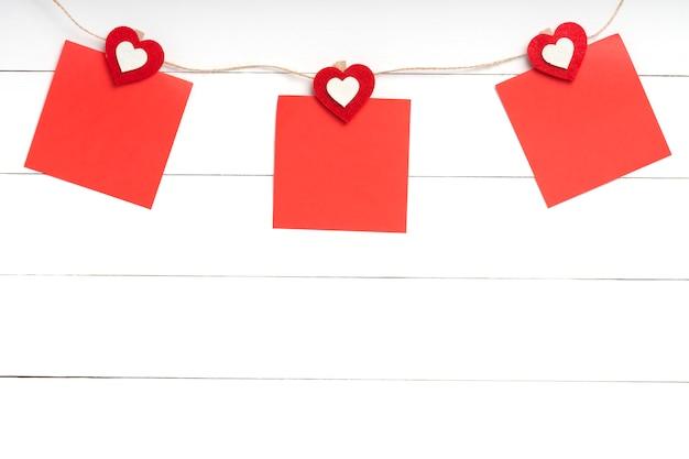 Комплект 3 пустых стикеров вися на строке с зажимками для белья за белой деревянной поверхностью. бумажные записки на веревке с красным сердцем. копирование пространства, вид сверху.