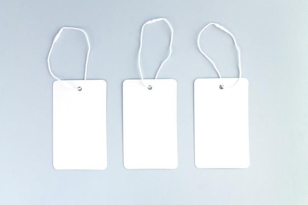 Набор из трех чистых белых бумажных тканевых этикеток или ценников на сером фоне
