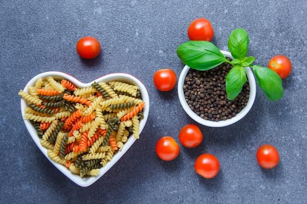 灰色の表面にハート型のボウルにトマト、黒胡椒、葉、カラフルなマカロニパスタのセット。上面図。