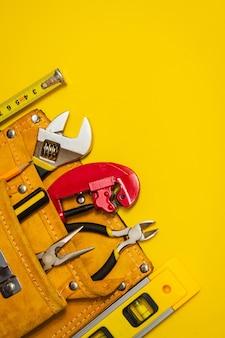 修理または建設の前に配管工のマスターマスター電気技師によって準備された黄色の背景にスエードバッグのツールのセット