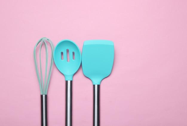 Набор инструментов для приготовления пищи на розовый. силиконовые лопасти с металлическими ручками и венчиком. вид сверху. копировать пространство