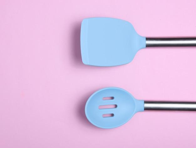 Набор инструментов для приготовления пищи на розовый. силиконовые лопасти с металлическими ручками. вид сверху. копировать пространство