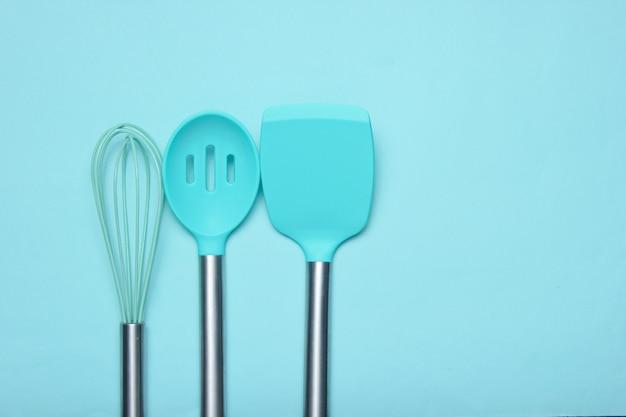 Набор инструментов для приготовления пищи на синем. силиконовые лопасти с металлическими ручками и венчиком. вид сверху. копировать пространство