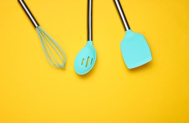 Набор инструментов для приготовления пищи на желтом. силиконовые лопасти с металлическими ручками и венчиком. вид сверху. копировать пространство