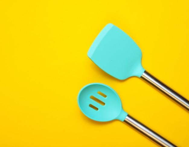 Набор инструментов для приготовления пищи на желтом. силиконовые лопасти с металлическими ручками. вид сверху. копировать пространство