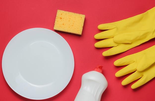 赤いスタジオの背景に皿を洗うためのツールのセットです。プレート、ゴム手袋、スポンジ、ボトル。上面図。フラットレイ