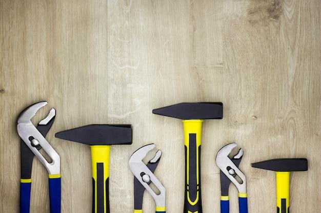 Набор инструментов на деревянном столе. молотки и гаечные ключи. сантехнические инструменты.
