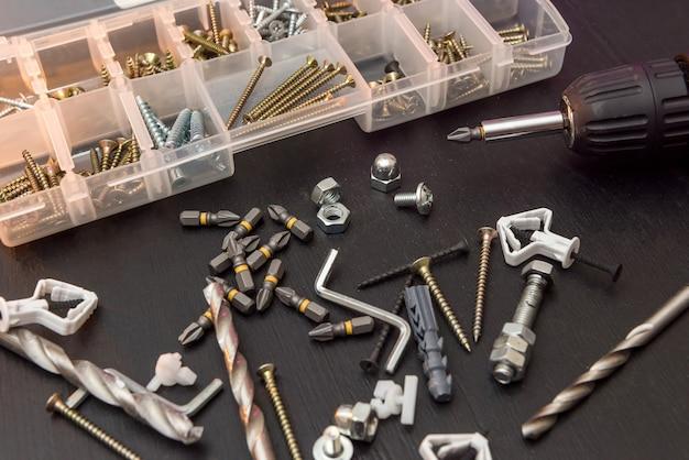 Набор инструментов на столе, отвертка с набором сверл и шурупы с болтами. все на ремонт