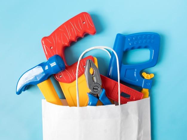 Набор игрушечных инструментов для мальчика в пакете. концепция родителей, покупающих игрушки для детей.