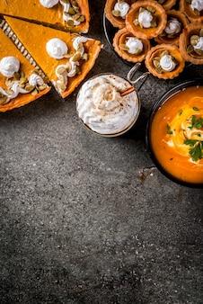 Набор традиционных осенних блюд. хэллоуин, день благодарения. пряный тыквенный латте, тыквенный пирог и тарталетки со взбитыми сливками и тыквенными семечками, тыквенный суп, на черном каменном столе. скопировать вид сверху