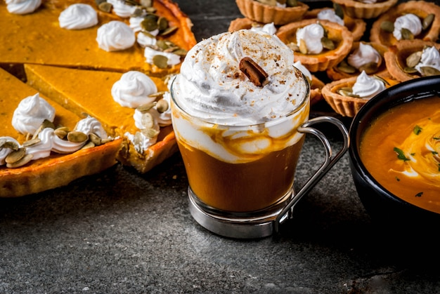 Набор традиционных осенних блюд. хэллоуин, день благодарения. пряный тыквенный латте, тыквенный пирог и тарталетки со взбитыми сливками и тыквенными семечками, тыквенный суп, на черном каменном столе. копировать пространство