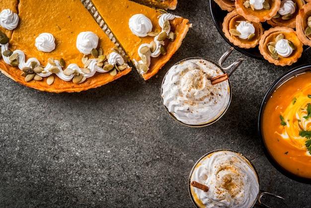 Набор традиционных осенних блюд. хэллоуин, день благодарения. пряный тыквенный латте, тыквенный пирог и тарталетки со взбитыми сливками и тыквенными семечками, тыквенный суп, на черном каменном столе. copyspace вид сверху