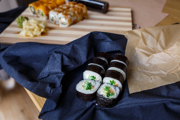 伝統的な日本料理のセットです。巻き寿司、にぎり、生鮭、ご飯、クリームチーズ、アボカド、生姜のピクルス。