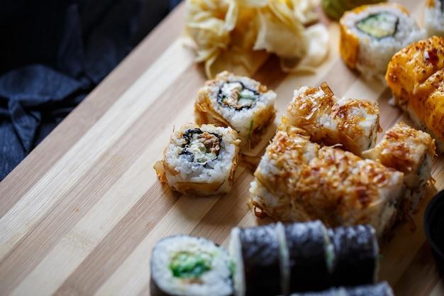 Набор традиционных японских блюд на темном фоне. суши-роллы, нигири, стейк из сырого лосося, рис, сливочный сыр, авокадо, лайм, маринованный имбирь. рамка азиатской еды.