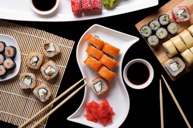 Набор традиционной японской кухни на темном столе. суши роллы, нигири, сырой стейк из лосося, рис, сливочный сыр, авокадо, лайм, маринованный имбирь.