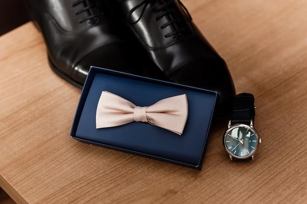 トレンディな紳士服とアクセサリーのセット。新郎の蝶ネクタイ、黒い靴、木製の背景にカフスのセット。新郎の朝。セレクティブフォーカス。