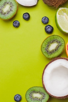 トロピカルフルーツのキウイ、ブラッドオレンジ、ココナッツ、マンゴー、ブルーベリー、ライム、緑の壁のセット。トロピカルフルーツ食品フレーム。 copyspaceとflatlay。免疫の概念。免疫力強化のための果物。ポップ