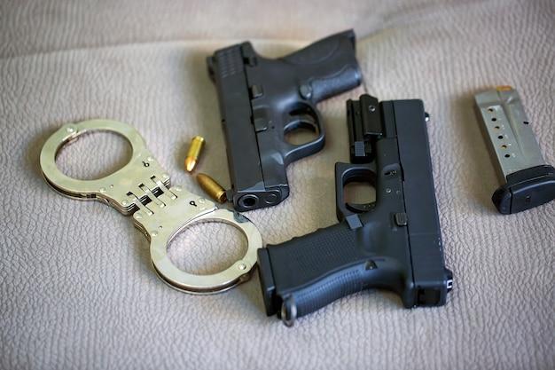 탄약, 경찰 수갑, 9mm 총알 포탄이 있는 두 개의 검은색 총 권총 세트. 반자동 권총 총기는 소파 배경에 서로 마주보고 있습니다. 카메라는 수갑에 초점을 맞춥니다.