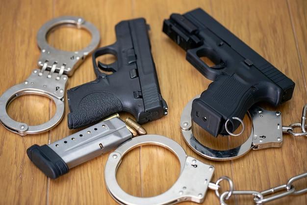 탄약이 있는 반자동 권총 2개와 나무 탁자에 경찰 수갑 2개 세트. 총 및 총알 껍질 9mm. 범죄, 계약 살인, 유급 암살자, 전쟁, 글로벌 무기 거래 및 무기 판매