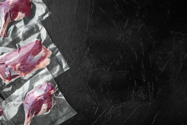 真空調理の準備ができている真空シールされた肉のセット。アヒルの胸肉、脚、生肉、黒い石のテーブル、上面図フラットレイ