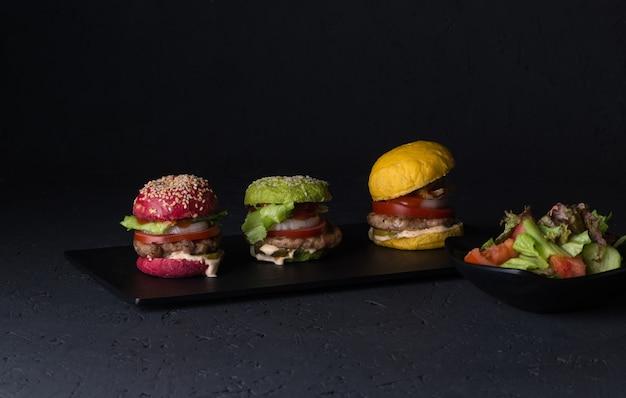 黒の背景の上の平板にさまざまな色のチーズバーガーのセット