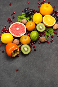 さまざまな、色とりどりのエキゾチックなフルーツのセット。みかん、グレープフルーツ、ライチ、キウイ、フダンソウの葉のブドウ。黒の背景。上面図コピースペース