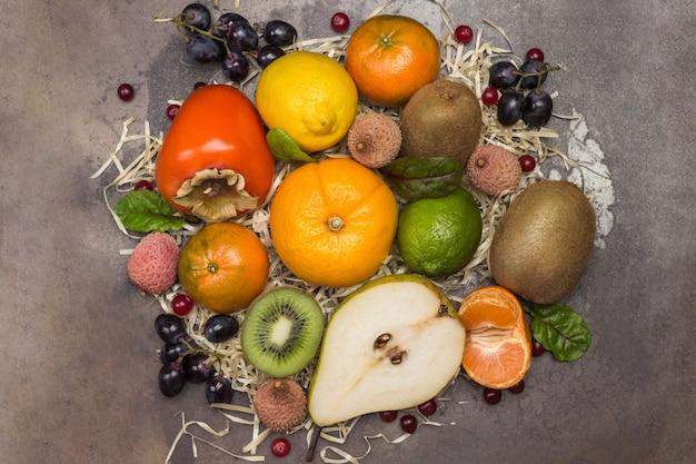 さまざまな、色とりどりのエキゾチックなフルーツのセット。マンダリン、グレープフルーツ、ライチ、キウイ、フダンソウの葉のあるブドウ。フラットレイ