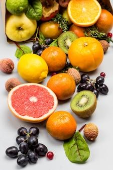 さまざまな、色とりどりのエキゾチックなフルーツのセット。みかん、グレープフルーツ、ライチ、キウイ、フダンソウの葉のブドウ。灰色の背景。上面図