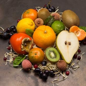 さまざまな、色とりどりのエキゾチックなフルーツのセット。みかん、グレープフルーツ、ライチ、キウイ、フダンソウの葉のブドウ。さびた金属の背景。フラットレイ
