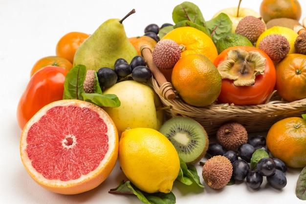 さまざまな、色とりどりのエキゾチックなフルーツのセット。みかん、グレープフルーツ、ライチ、キウイ、フダンソウの葉のブドウ。白色の背景。上面図クローズアップ