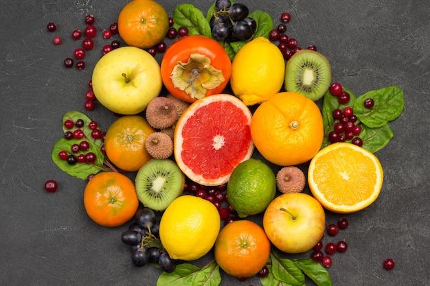 さまざまな、色とりどりのエキゾチックなフルーツのセット。みかんとオレンジ、キウイとナシ、柿とライチ。黒の背景。フラットレイ
