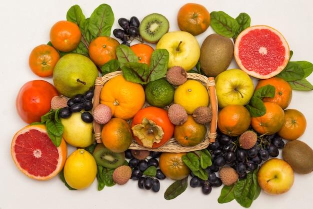 さまざまな、色とりどりのエキゾチックなフルーツのセット。みかん、グレープフルーツ、ライチ、キウイ、フダンソウの葉のブドウ。白色の背景。フラットレイ