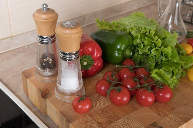 Набор разнообразных овощей на разделочной доске на кухне. концепции здорового питания. ингредиенты для салата, помидоры, перец, специи
