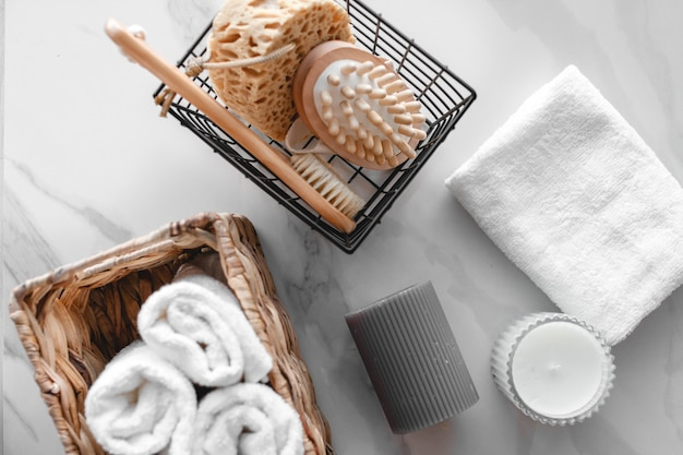 Набор различных банных принадлежностей. махровое полотенце, мыло, расческа, масло, шампунь, мочалка мочалки и свечи. вид сверху