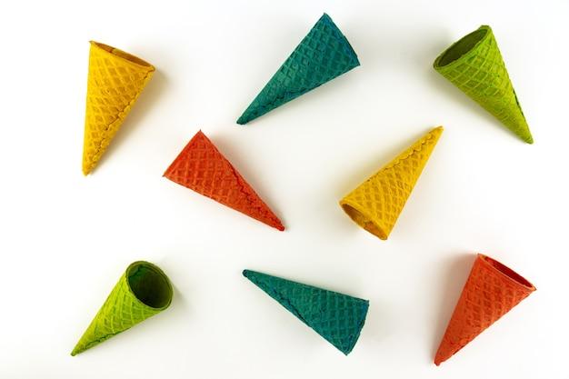 Набор различных ярких разноцветных вафельных рожков мороженого на белом