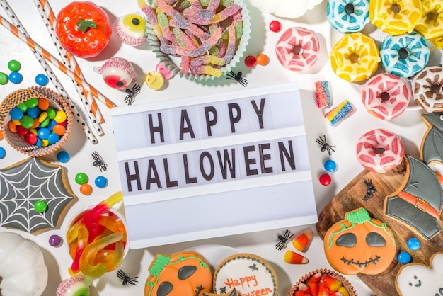 Набор различных классических удовольствий хэллоуина на белом фоне. подборка ассортимента традиционного печенья, имбирных пряников, конфет, конфет и декора из тыкв. кошелек или жизнь концепция, вид сверху копией пространства