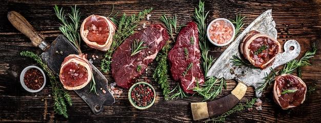 さまざまな古典的な生の肉、子牛のビーフステーキ、ビーフのランプステーキ、ダークウッドの背景の古い肉肉屋で提供されるテンダーロインフィレミニョンのセット。バナー、メニューレシピ上面図。