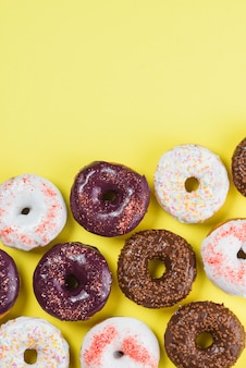 Set of various colorful donuts on yellow background