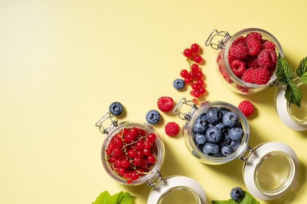 Набор различных свежих сезонных ягод в стеклянных банках здоровое питание