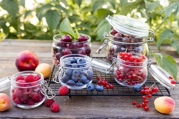 Набор различных свежих сезонных ягод в стеклянных банках на садовом столе