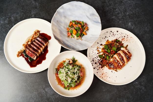 Набор различных тарелок с едой на сером фоне стола с копией пространства
