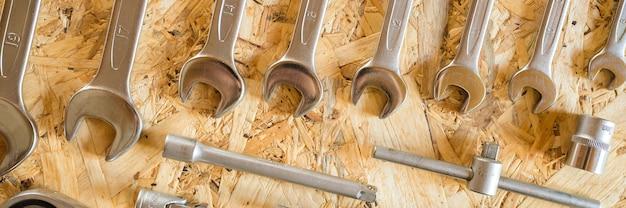 さまざまな修理用ハンドツールまたは自動車整備士のツールのセット。修理ツールキット。建物の設備。木製の背景、パターン、上面図。バナー