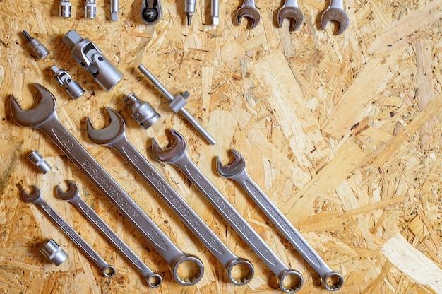 さまざまな修理用ハンドツールまたは自動車整備士のツールのセット。修理ツールキット。建物の設備。木製の背景、パターン、上面図。テキスト用のスペース