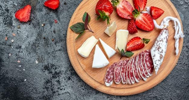様々なスペインの乾燥硬化フエサラミソーセージスライス、カマンベールチーズ、イチゴのセット。長いバナー形式。上面図。